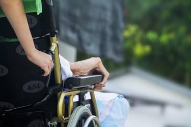 betagte Person im Rollstuhl, geschoben von einer jüngeren Person