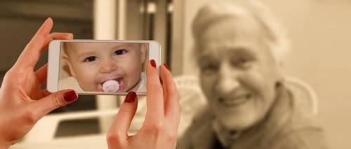 Alte Frau ist, betrachtet durch das Smartphone, jung