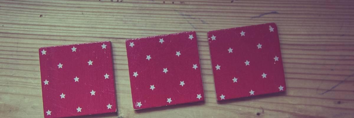 Drei rote Memorykarten liegen auf einem Tisch.