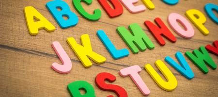 Bunte Buchstaben liegen auf einer Holzunterlage